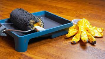gele handschoenen en werkblad met verf en roller foto