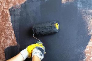 hand schildert de muren met een rolgrijze kleur foto