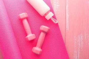 roze stomme bellen, waterfles en yogamat foto