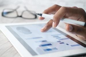hand bezig met digitale tablet op kantoor, met behulp van zelfgemaakte grafiek