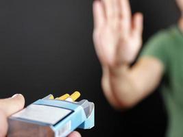 hand van een meisje houdt een pakje sigaretten vast stelt voor om een keuze te maken foto