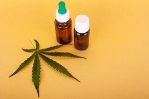 medicinaal cannabisextract met thc en cbd op gele achtergrond foto