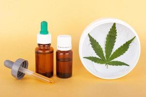 medicinale cannabiscrème en extract met thc en cbd op gele achtergrond foto
