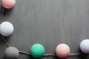 slinger met kleurrijke katoenen ballen van pastelkleuren op een grijze achtergrond foto