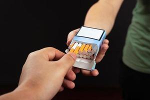 hand neemt een sigaret uit een pak op een donkere achtergrond foto