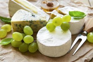 verschillende soorten kaas, basilicum en druiven foto