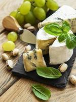 verschillende soorten kaas, druiven en noten foto