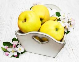 doos met appels en appelboom bloesem op een houten tafel foto