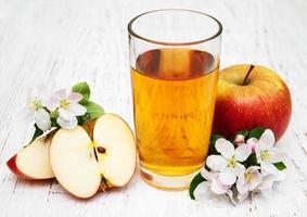 glas appelsap met appels en bloemen op een houten achtergrond foto