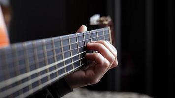 vrouwelijke hand houdt een akkoord op een akoestische gitaar foto