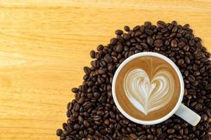 bovenaanzicht van een mok koffie met bonen op houten achtergrond foto