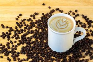 bovenaanzicht van een mok koffie met bonen op houten achtergrond. foto