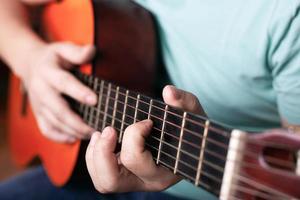 het spelen van de akoestische gitaar close-up, de hand grijpt het akkoord, het bespelen van een muziekinstrument foto