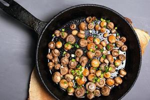 gebakken champignon champignons besprenkeld met kruiden in een zwarte pan op een grijze achtergrond foto