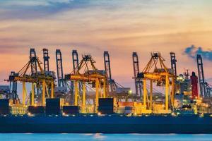vrachtschip dat lading laadt bij laaddok op schemertijd in singapore foto