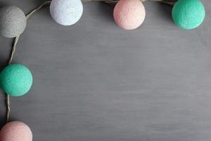 slinger met katoenen kleurrijke ballen van pastelkleuren op een grijze achtergrond foto