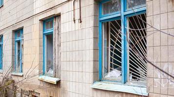 oude gebroken ramen met metalen staven van een verlaten ziekenhuisgebouw foto