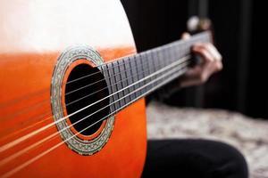 het spelen van de klassieke Spaanse akoestische gitaar in oranje kleur foto