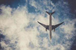vliegtuig op blauwe hemel met wolken