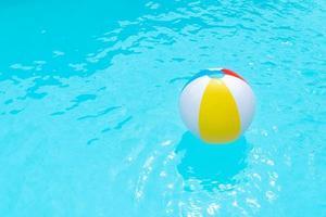 strandbal drijvend op het wateroppervlak van een zwembad foto