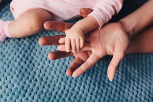 mama en papa houden de hand van de baby vast. handvat voor kinderen foto