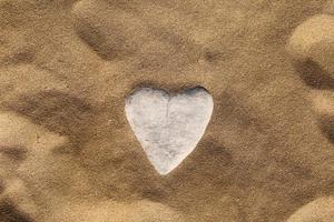 steen in de vorm van een hart op zand. zeezand achtergrond, behang. Valentijnsdag, bruiloft, huwelijksreis of liefde wenskaart concept. foto