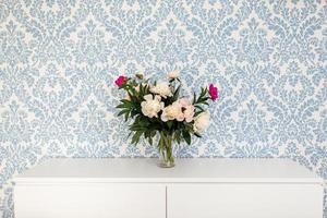 pioenrozen verse snijbloemen in een vaas met kopie ruimte op een witte tafel op blauwe achtergrond. foto