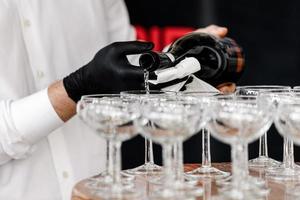 hand met een zwarte handschoen gieten champagne in het restaurant. ober in zwarte handschoenen champagneglazen gieten op de houten tafel. selectieve aandacht. foto