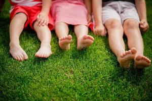 blote benen van kleine meisjes die op het gras zitten. foto