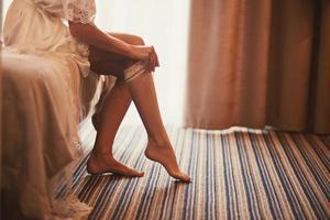 vrouw met een kousenband op haar been. de bruid houdt een losse kousenband in de hand in een hotelkamer. ochtend voorbereiding bruiloft concept. foto