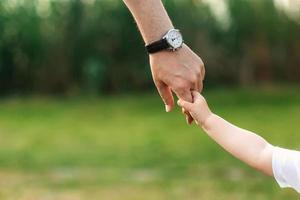 vader die zijn kind bij de hand houdt. een wandeling in de natuur foto