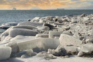 brokken ijs op een strand met een kleurrijke bewolkte hemel foto