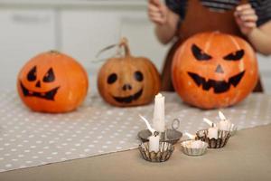 brandende kaarsen close-up op een achtergrond van pompoenen. halloween pompoen hoofd hefboom lantaarn met brandende kaarsen. verlichte halloween-pompoenen met kaarsen in de keuken foto