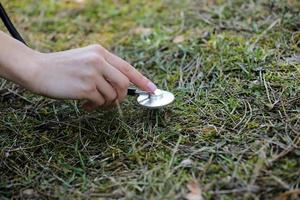 hand van een vrouw luistert naar de grond met een stethoscoop in het park. concept van liefde voor het milieu. selectieve aandacht. kopieer ruimte. foto