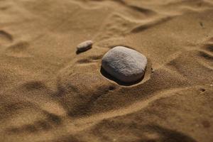stenen op de achtergrond van het zandstrand. natuurlijk behang, textuur. selectieve aandacht. kopieer ruimte. foto