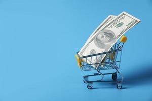 dollarbiljetten in de winkelwagen bij het winkelen geïsoleerd op een blauwe achtergrond. close-up van het winkelwagentje. geneeskunde concept met kopie ruimte foto