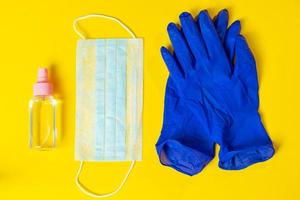 latex handschoenen, medisch gezichtsmasker en antiseptisch middel op gele achtergrond foto