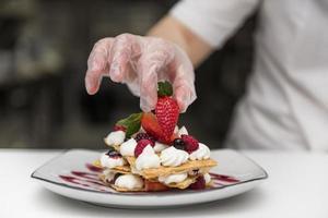 chef-kok aardbei op dessert zetten. resolutie en mooie foto van hoge kwaliteit