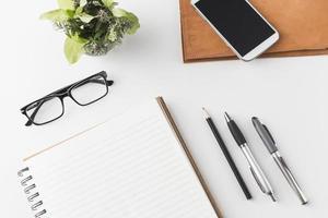 smartphone en bril in de buurt van briefpapier en een plant. resolutie en mooie foto van hoge kwaliteit