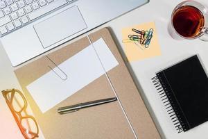 map met wit papier voor notities, kantoorbenodigdheden, theekop, notitieboekje en toetsenbord op bureau foto