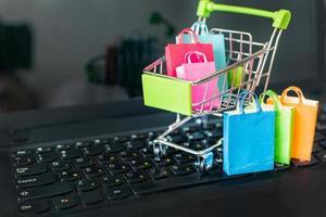 gekleurd papier boodschappentassen in winkelwagen op een laptop computertoetsenbord. online winkelen vanaf sites via het internetconcept. foto