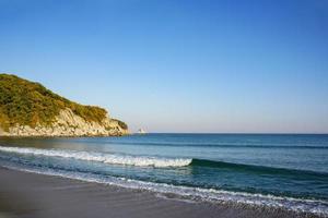golven op het strand en de bergen op de achtergrond bij de zee van japan foto