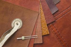 bovenaanzicht van leer en naalden om te naaien, kopieer ruimte foto