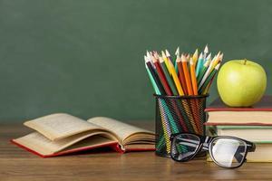kleurpotloden en appel op het bureau van de student foto