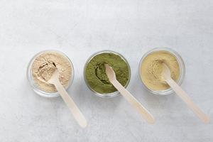matcha en voedingspoeders in kommen op neutrale achtergrond foto
