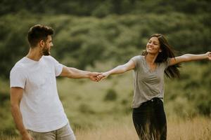 gelukkig jong koppel verliefd wandelen door grasveld foto