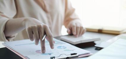 close-up van een professional die grafieken bekijkt en een rekenmachine gebruikt foto