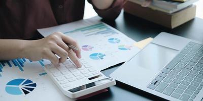 close-up van een hand op een rekenmachine met grafieken op een bureau foto