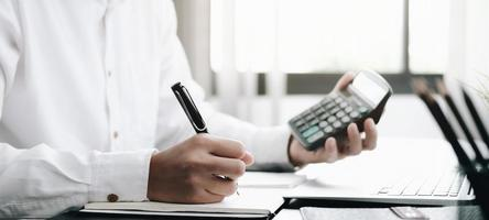 close-up van een professional die een rekenmachine bekijkt en aantekeningen maakt foto