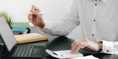 close-up van een zakenman met behulp van een rekenmachine en een tablet foto
